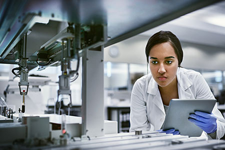 A lady in a white coat and with plastic gloves looks at a sterile production situation while holding a touch.