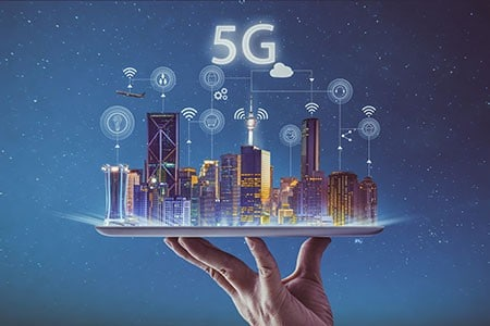 A hand is holding a plate with a city on top. Above the city digital icons symbolising 5G.